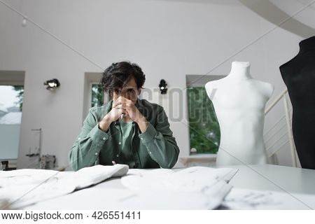 Thoughtful Tailor Sitting Near Blurred Sewing Patterns And Tissue In Atelier