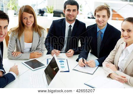Image of business partners sitting at workplace and looking at camera