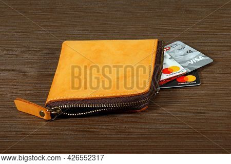 London, United Kingdom - March 15, 2021: Stack Of Credit And Debit Bank Cards Inside Leather Wallet