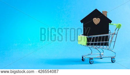 Model Of A House In A Mini Cart On A Light Blue Background With Space For Text. Investments In Resid