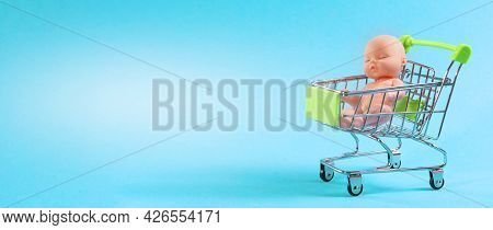 Baby Doll In A Basket On A Blue Background With Place For Text. Buy A Child