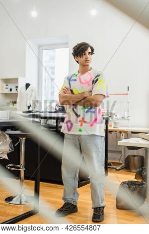 Young, Serious Fashion Designer Standing With Crossed Arms In Atelier