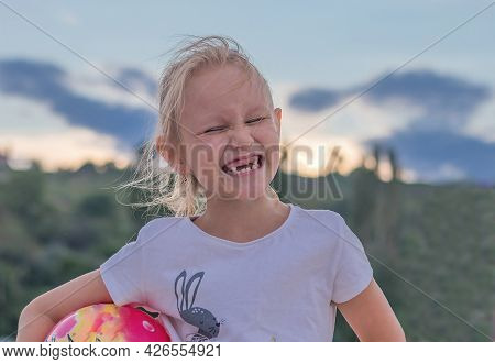 Girl, 6 Years Old, Laughing Cheerfully With A Toothless Mouth, Squinting Her Eyes, Portrait Of A Chi