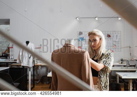 Young, Blonde Fashion Designer Near Mannequin In Atelier