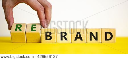 Time To Rebrand Symbol. Businessman Turns Wooden Cubes And Changes The Word 'brand' To 'rebrand'. Be