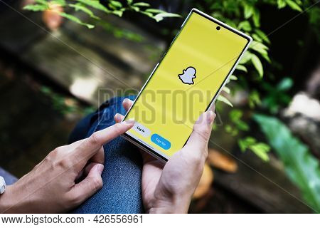 Chiang Mai, Thailand -july 09, 2021: A Hand Holding A Smartphonei Mobile Which Displays The Snapchat
