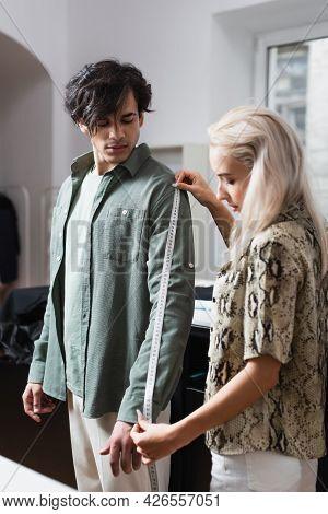 Young Man Near Blonde Designer Measuring Him In Atelier