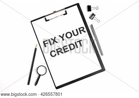 On A White Background Magnifier, A Pen And A Sheet Of Paper With The Text Fix Your Credit , . Busine