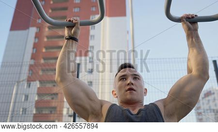 Young Muscular Man Pulls Himself Up On The Horizontal Bar Of The City Playground. A Young Man Pulls