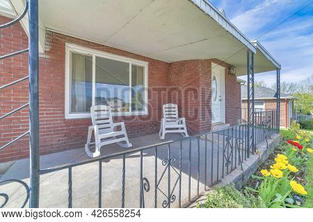 Rocking Chairs On The Front Porch Of A House With Red Brick Wall And White Door