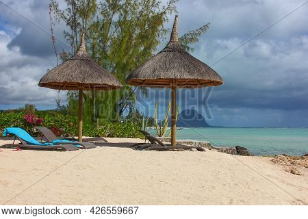 Beautiful Tropical White Sandy Beach With Exotic Plants, Sunbeds And Beach Umbrellas Before Thunders