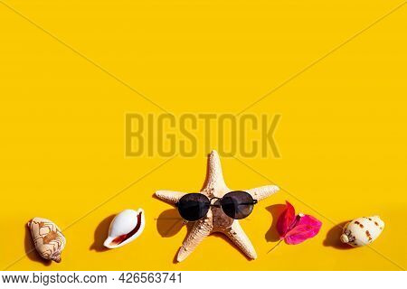 Composition Of Starfish With Sunglasses And  Flower With Exotic Seashells On Yellow Background.