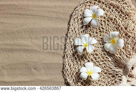 Summer Background Concept. Plumeria Flowers On Mesh Beach Bag On Sand.