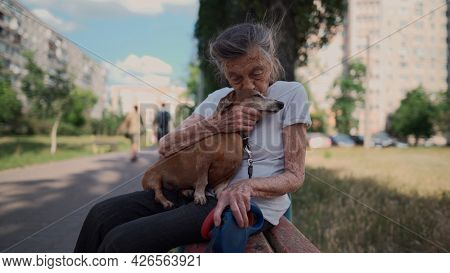 Senior 90-year-old Woman With Gray Hair And Deep Wrinkles Sits Outdoors In Assisted Living Facility
