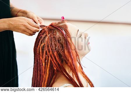Process Of Braiding Braids On Head In Beauty Salon Close Up. Red-haired Girl Makes Braids-dreadlocks