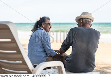 Happy Asian Family, Senior Couple Sitting On Chairs With Backs On Beach Travel Vacation Talking Toge