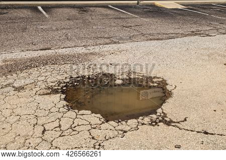 A Large Pot Hole In The Road With Cracks And Filled With Water In A Lot