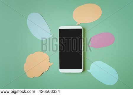 White Smart Phone With Clipping Path On Touchscreen ,  Multi Color Speech Bubbles  Paper On Green Ba