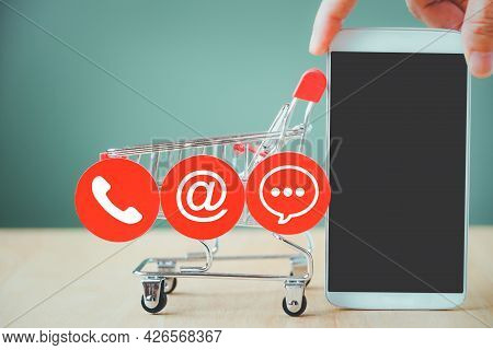 Hand Holding Mobile Phone And Contact Symbol On Red Circle Paper  With Blurred Shopping Cart For Con