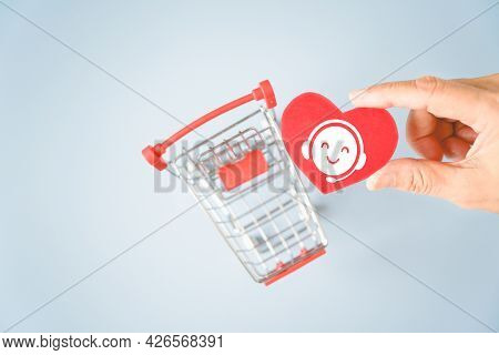 Human's Hand Holding Call Center Symbol On Red Heart Paper Cut With Blurred Shopping Cart, Service M