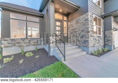 Two Storey Home Facade With Stone Brick Wall And Glass Paned Gray Front Door