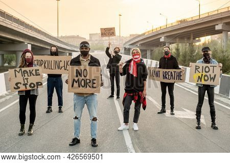 Group of young multi-ethnic people in cloth masks standing on road while protesting on street