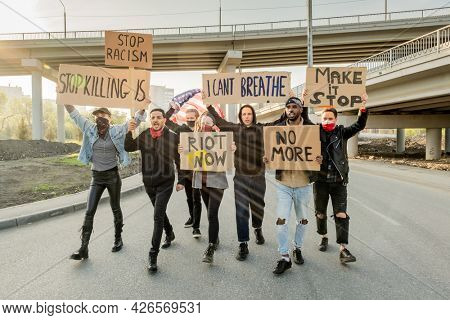 Group of angry young multi-ethnic people raising cardboard banners while protesting against racism at street demonstration