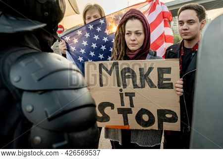Serious young Caucasian woman with dreads holding banner with Make Stop Words standing with other activists in front of police forces outdoors