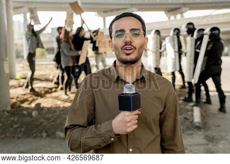 Portrait of young mixed race journalist with beard speaking into microphone while covering riot: protestors arguing with riot police in background