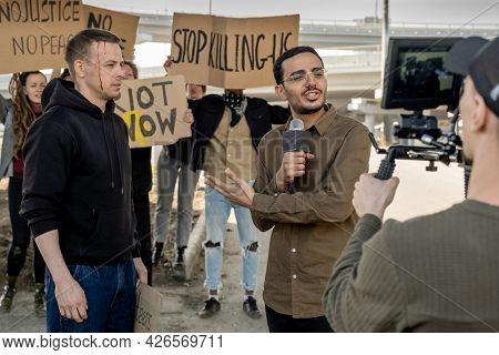 Young mixed race journalist with microphone pointing at protestor with broken head while covering riot for TV channel