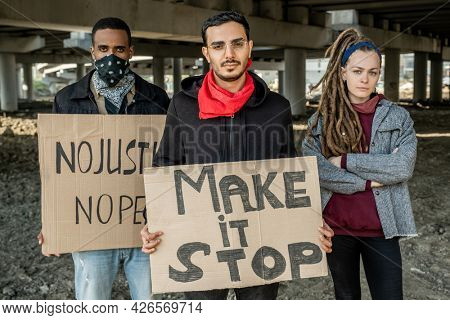Confident young multi-ethnic rebellion people standing with signs and protecting against unfair of government