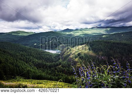 Mountain Lake Uchkel Is Surrounded By Mountains And Coniferous Taiga. Ulagan District Of The Altai R