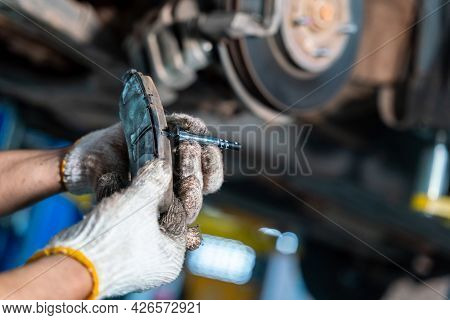 Car Mechanic Or Serviceman Checking A Disc Brake And Asbestos Brake Pads It's A Part Of Car Use For