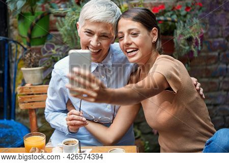 young adult caucasian female and elderly woman smiling, looking at cell phone,  taking selfie,  smiling, sitting in outdoor cafe.  colorful background