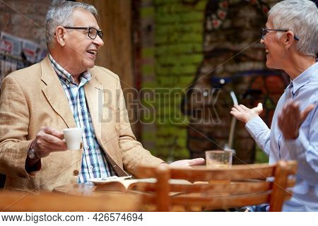senior caucasian couple talking in outdoor cafe, smiling, drinking coffee, looking each other