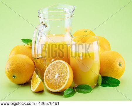Yellow orange fruits and fresh orange juice isolated on light green background.