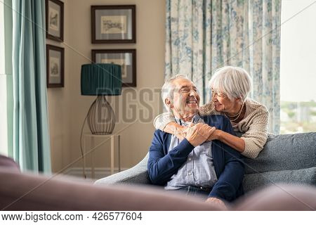 Happy senior woman embracing her husband at home while laughing together. Smiling wife hugging old man sitting on couch from behind. Joyful retired couple having fun while looking at each other.
