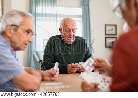 Retired senior man in wheelchair playing cards with his friends at nursing home. Group of old friends playing cards at care centre. Focused senior people playing cards game during afternoon.