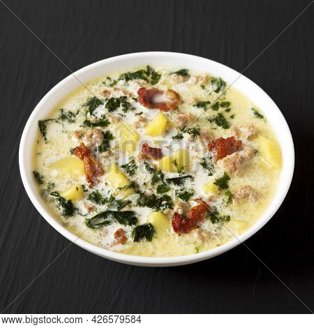 Homemade Zuppa Toscana With Kale And Bread In A White Bowl On A Black Background, Side View.