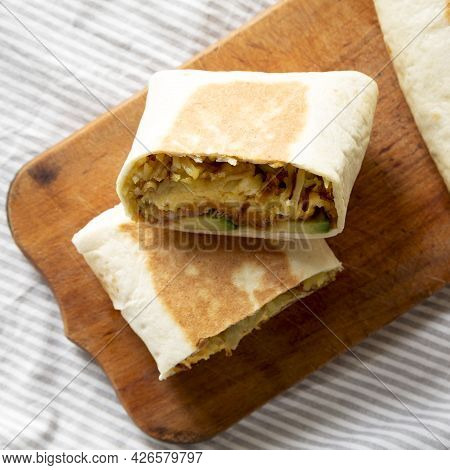 Homemade Breakfast Egg Burrito With Avocado And Bacon On A Rustic Wooden Board, Top View. Overhead,
