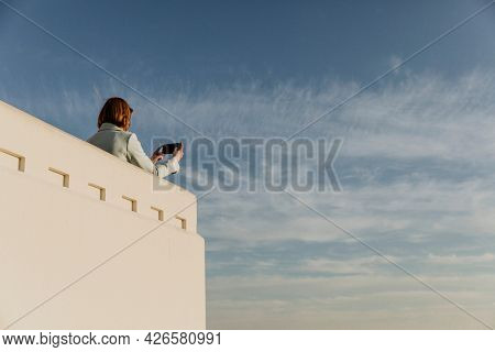 Woman capturing the Los Angeles view with her phone at the Griffith Observatory, USA