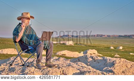 Senior man in Mexican poncho and cowboy hat is sitting on a folding chair and working on laptop in the middle of nowhere, early morning in the badlands of Pawnee National Grassland in Colorado