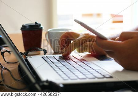 Worker Work At Home With Laptop And Using Mobile Calling  To His Staff At Office