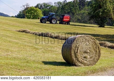 Aadorf, Switzerland June 17, 2021 Blue Tractor With Red Trailer On A Field, Farm Machinery Harvestin