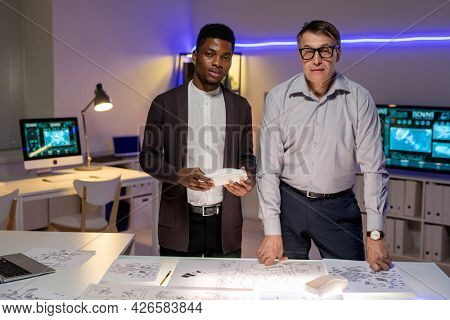 Team of serious multi-ethnic industrial designers standing at table with blueprints and analyzing 3D car model