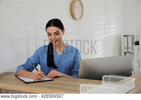 Receptionist With Clipboard At Countertop In Hospital, Space For Text