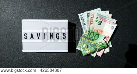 Lightbox Board With Word Savings In Black Letters Around Euro Banknotes. Money, Business, Finance, I