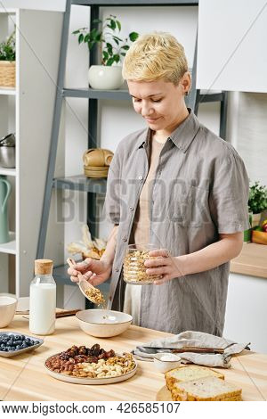 Healthy young woman preparing muesli by kitchen table