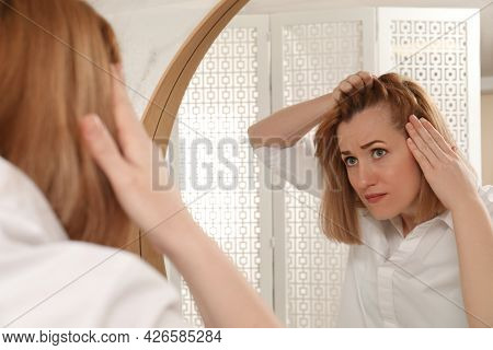 Emotional Woman Suffering From Baldness Near Mirror At Home
