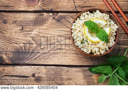 Boiled Bulgur With Fresh Lemon And Mint On A Plate. A Traditional Oriental Dish Called Tabouleh. Woo
